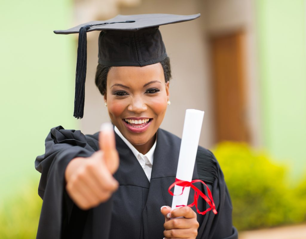 beautiful african female graduate giving thumb up at graduation ceremony
